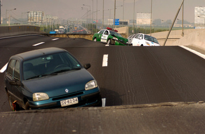 Vehicles sit on a destroyed motorway in Santiago following a powerful earthquake in southern Chile, Saturday, Feb. 27, 2010. (AP Photo/Carlos Espinoza)